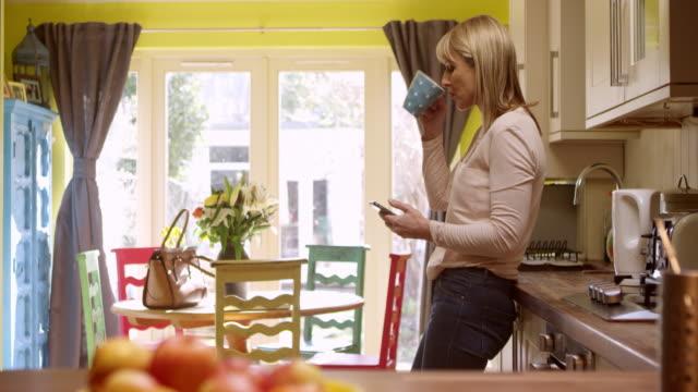 mogen kvinna sms på mobiltelefon på hem skott på r3d - working from home bildbanksvideor och videomaterial från bakom kulisserna