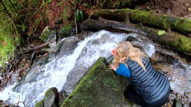 Mature woman traverses top of waterfall, in forest