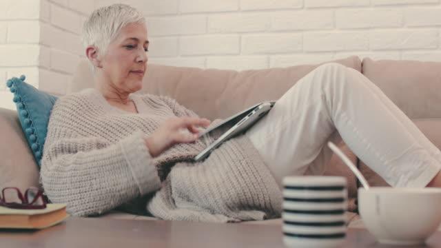 donna matura che digita e-mail sul laptop e fa un pisolino sul divano. - sonnecchiare video stock e b–roll