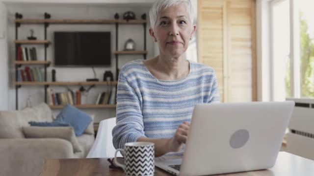 dizüstü bilgisayarda yazarak ve kameranın doğru başparmak gösterilmesini olgun kadın. - thumbs up stok videoları ve detay görüntü çekimi