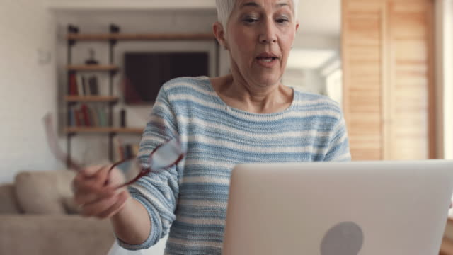 Mature woman typing on laptop in the living room. video