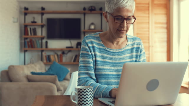 Mature woman typing on laptop while surfing the internet at home. video