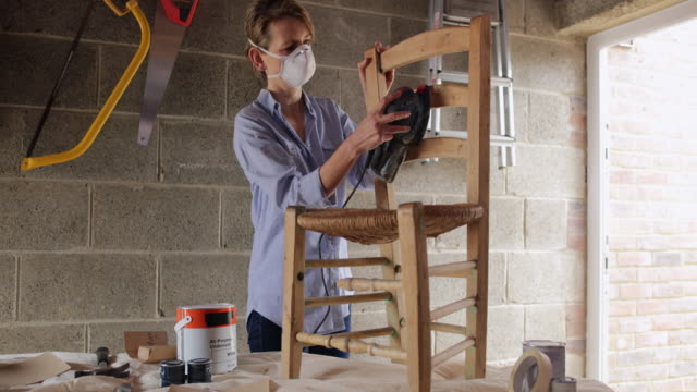 Mature Woman Upcycling Furniture In Workshop At Home Using Electric Sander Mature Woman Upcycling Furniture In Workshop At Home Using Electric Sander power tool stock videos & royalty-free footage