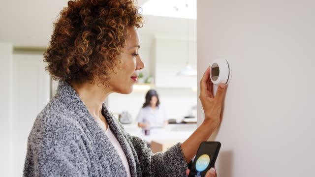 olgun kadın arka planda eşcinsel ortağı ile evde dijital merkezi ısıtma termostat kontrol etmek için telefonda uygulama kullanarak - yavaş çekim de vuruldu - ayarlamak stok videoları ve detay görüntü çekimi