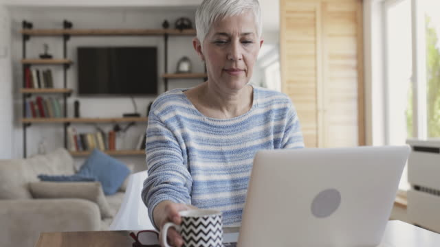 Mature woman using computer and drinking coffee at home. video
