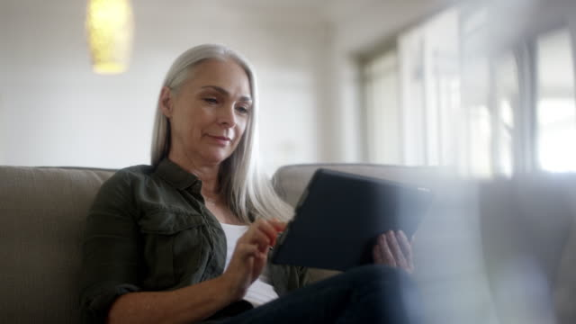 vídeos y material grabado en eventos de stock de mujer madura usando tableta digital en casa - usar la tableta digital