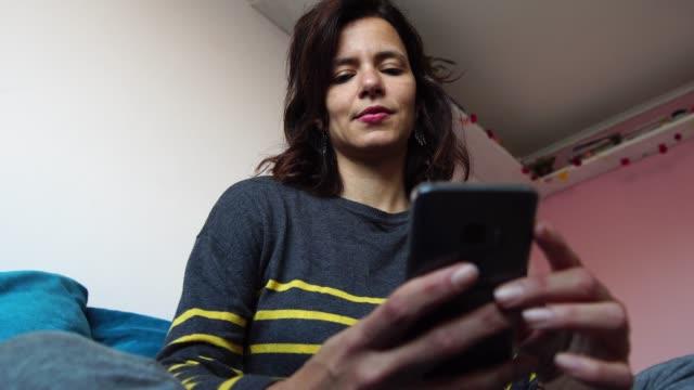 vidéos et rushes de mature femme à l'aide de son smartphone assis sur le canapé à la maison - portrait - 40 44 ans