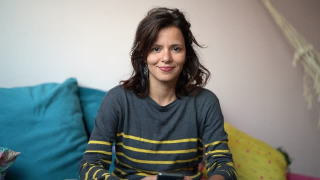 vidéos et rushes de mature femme à l'aide de son smartphone assis sur le canapé à la maison - portrait - portrait femme