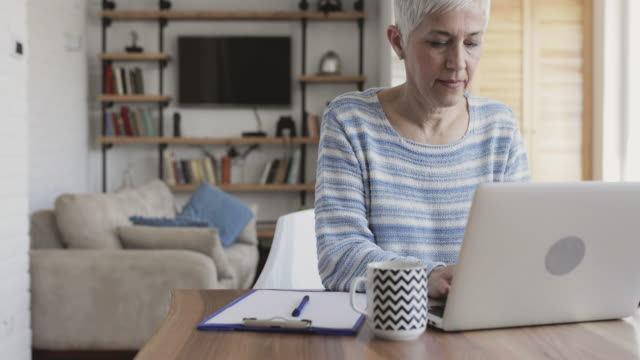 Mature woman using laptop and taking notes on the paper. video