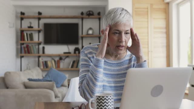 vidéos et rushes de femme mûre avec ordinateur portable à la maison et se sentir frustré sur un courriel qu'elle a reçu. - une seule femme d'âge mûr