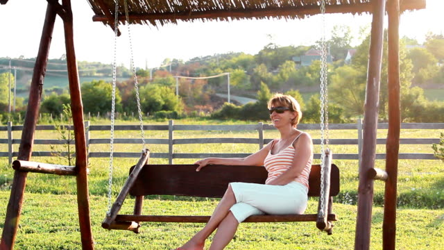 Mature woman Beautiful mature sitting on the bench and rocking. rocking chair stock videos & royalty-free footage