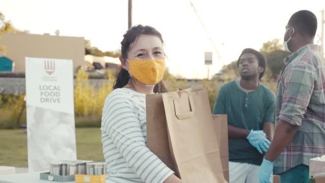 vídeos y material grabado en eventos de stock de mujer madura voluntaria durante la campaña de alimentos con la familia y amigos - food drive