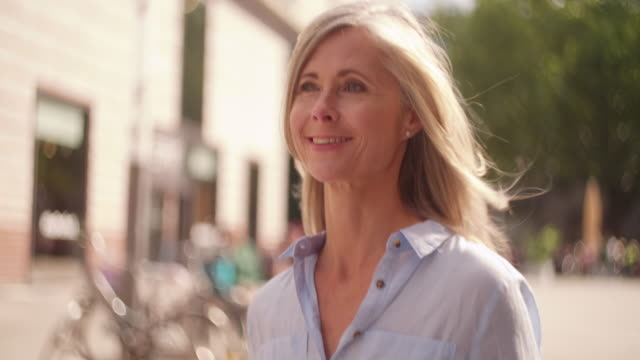 Mature woman walking confidently on a city street Smiling mature woman with grey hair walking confidently down a city street while holding shopping bags bolos stock videos & royalty-free footage