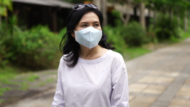 Mature woman walking on the street with surgical mask