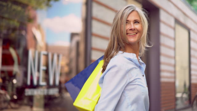Mature woman walking with shopping bags and waving goodbye video