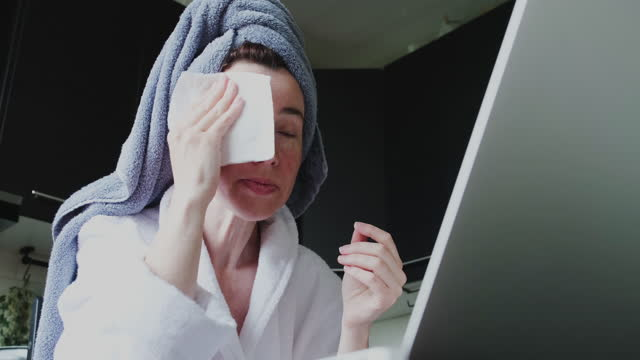 Mature woman wearing bathrobe and hair towel is sitting in domestic kitchen and drying her face with a tissue and communicating using laptop video