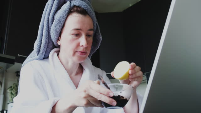 Mature woman wearing bathrobe and hair towel is sitting in domestic kitchen and communicating using laptop video