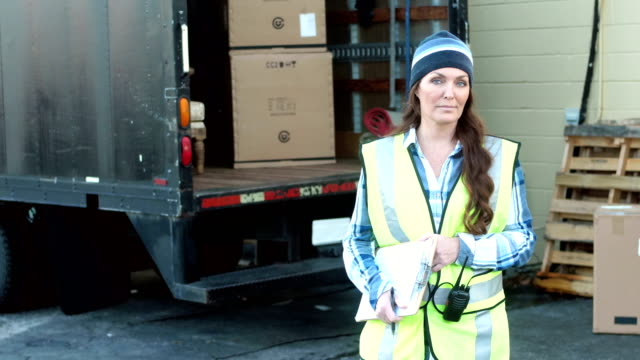 Mature woman with delivery truck writing on clipboard video