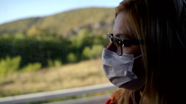 Mature woman with protective face mask in the bus-Corona virus travel concept