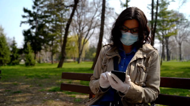 Mature woman with protective mask using a mobile phone outdoors video