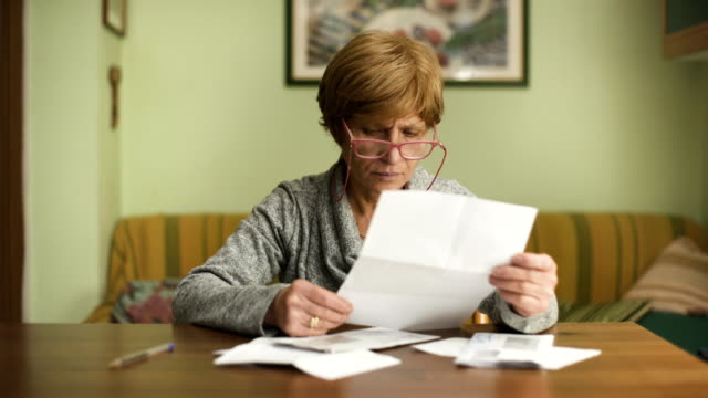 mature woman with red glasses looks worried about the bills to pay video