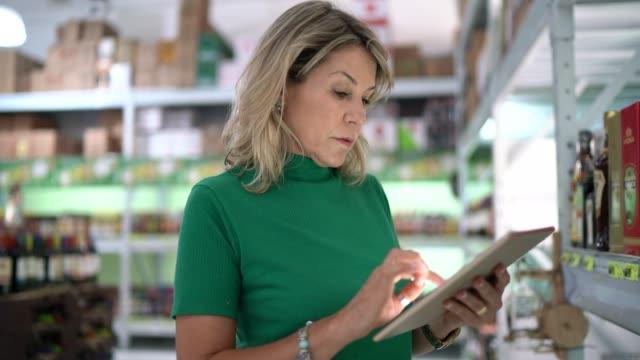 mogen kvinna arbetstagare gå och använda tablett på grossist - kameraåkning på räls bildbanksvideor och videomaterial från bakom kulisserna
