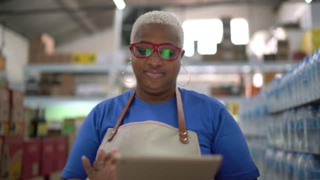vídeos de stock e filmes b-roll de mature woman worker walking and using tablet at wholesale - supermarket worker