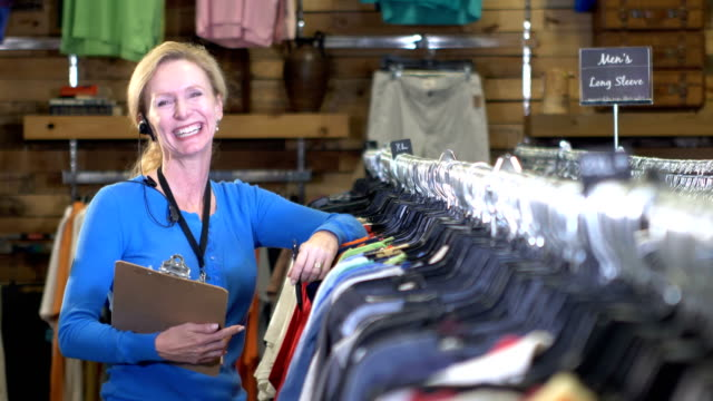 Mature woman working in clothing store taking inventory video