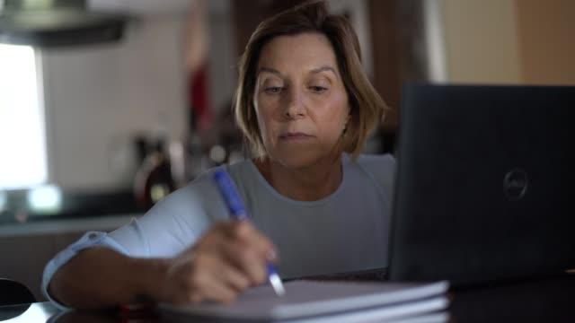 vidéos et rushes de femme mûre travaillant ou étudiant de la maison - une seule femme d'âge mûr