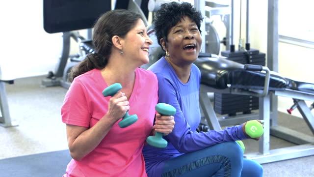 mogna kvinnor på gymmet träna, prata, skratta - gym skratt bildbanksvideor och videomaterial från bakom kulisserna