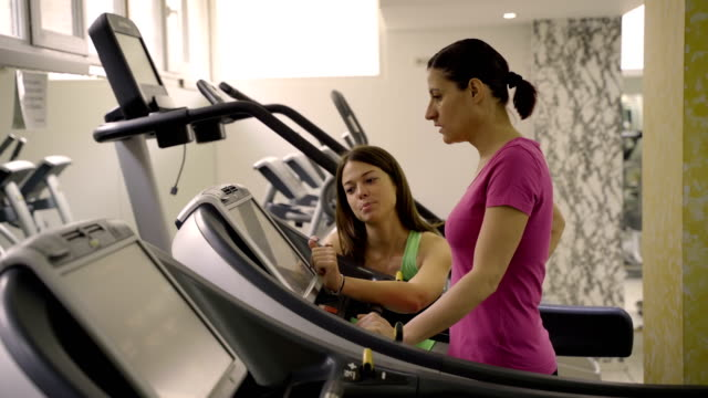 mature women have a cardio workout with personal trainer - runner rehab gym video stock e b–roll