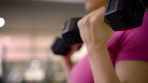 vídeos de stock e filmes b-roll de mature women have a dumbbell training with personal trainer.close up - exercitar