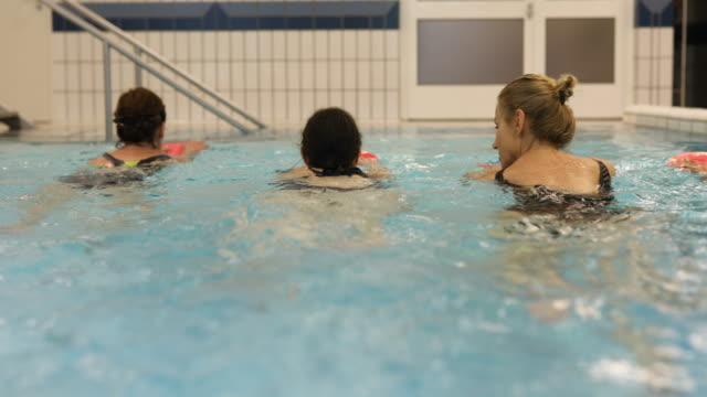 mature women holding floats while swimming in pool - 40 49 lat filmów i materiałów b-roll