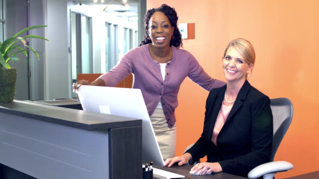 Mature women in office conversing over computer screen Two multi-ethnic mature women in an office at a cubicle or reception desk. A blond woman is sitting at a computer and her African-American coworker is standing beside her as they converse, pointing at the screen. They look up at the camera and smile. office cubicle stock videos & royalty-free footage