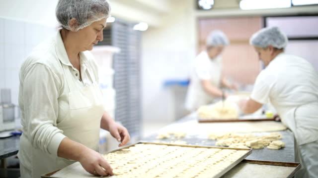 vidéos et rushes de femmes mûres faire des bretzels - boulanger