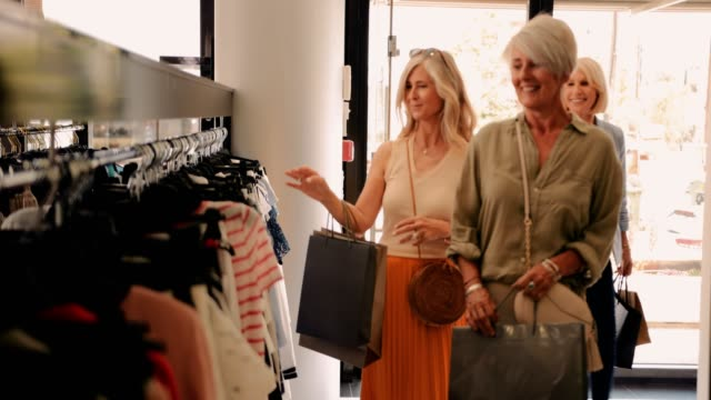 Mature women shopping and entering clothes store in the city
