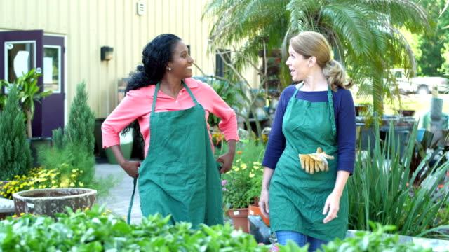 vídeos de stock e filmes b-roll de mature women walking in plant nursery, putting on apron - avental