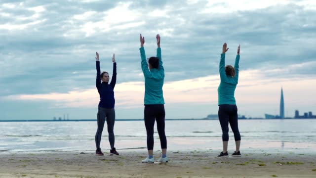 Mature yoga teacher explaining two adult female students how to do standing half forward bend with outstretched arms during practice near sea on beach in evening