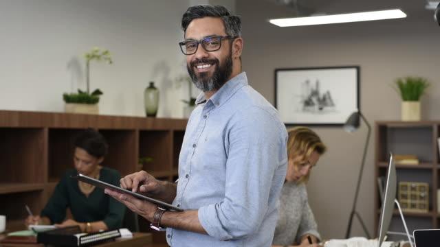 vidéos et rushes de homme d'affaires ayant subi une maturation de race mixte à l'aide de tablette numérique - 40 44 ans