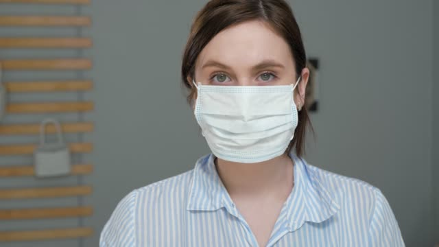 maximum protection for cold, flu, virus, acute respiratory infections, quarantine, epidemic, irony, sarcasm concept. attractive girl puts on surgical mask, then one more and one more ... - nakładać filmów i materiałów b-roll