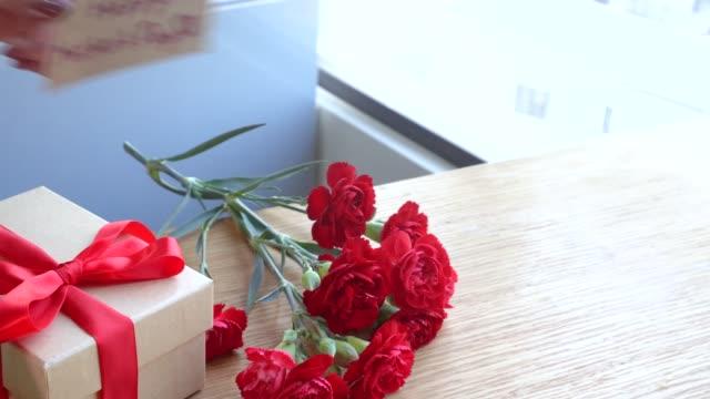 5月の母親の日のアイデアの写真-明るい近代的なテーブル、コピースペース、フラットレイ、トップビューに隔離された女性の手にロープの弓を保持することによって結ば美しい咲くカーネ� - 母の日点の映像素材/bロール