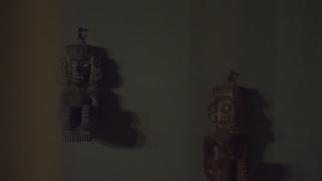 mayan or inca statue moving alone on a wall in a creepy haunted house on a winter night. halloween scary ambiance. ghost, demon or spirit. aztec historic civilization. shot on red scarlet 6k. - prodotto d'artigianato video stock e b–roll