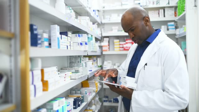 Maybe technology will help me decide which is best 4k video footage of a male pharmacist using a tablet while working in an apothecary pharmacist stock videos & royalty-free footage