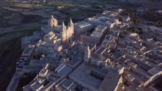 Mdina Aerial Jib Shot Drone shot flying over Mdina in Malta during sunset in a jib movement. People can be seen waling in the Cathedral Square malta stock videos & royalty-free footage
