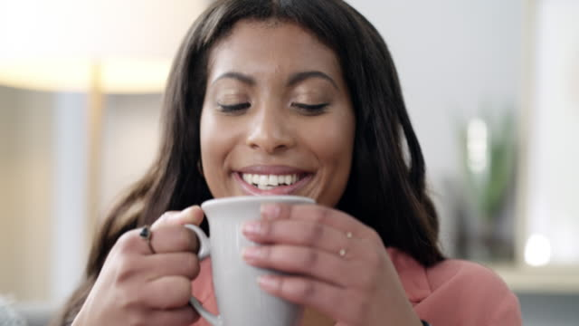 Me time is a must for peace of mind 4k video footage of a young woman enjoying enjoying a relaxing coffee break at home mug stock videos & royalty-free footage