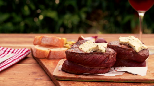 Meal of beef steak medallions with red wine Wooden table outdoors with a meal of tender beef steak medallions topped with herbed butter on a vintage wooden table with a glass of red wine beef stock videos & royalty-free footage