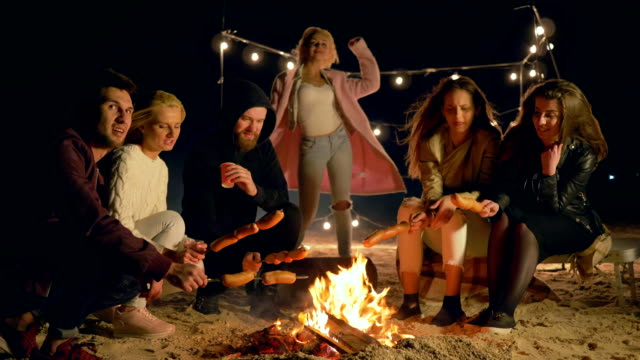 meal on fire, young people roast sausages at campfire while relaxing outdoors at night - falò spiaggia video stock e b–roll
