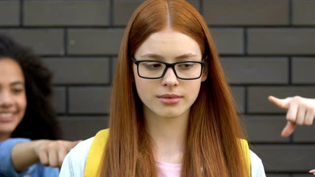 menar skolbarn pekar fingrar på smart girl, retas om glasögon - dom bildbanksvideor och videomaterial från bakom kulisserna