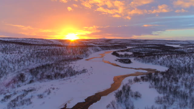 AERIAL: Meandering river flowing through gorgeous hilly winter landscape Lapland video