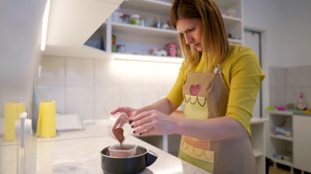 vídeos de stock e filmes b-roll de measuring ingredients for cake with kitchen scale - cacau em pó